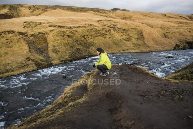 Мужской турист, приседающий на берегу реки, Скогафосс, Исландия — стоковое фото