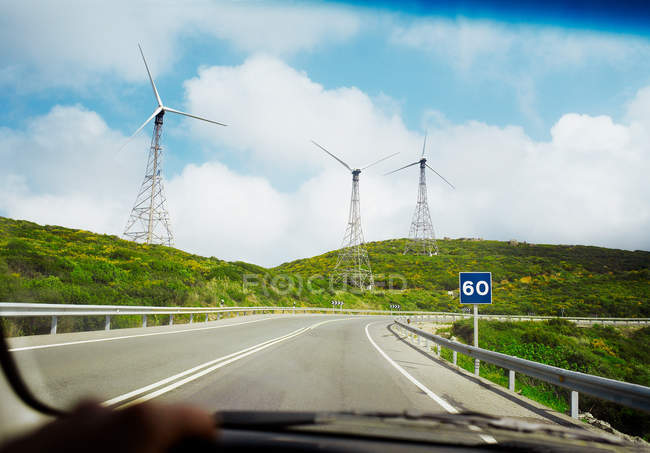 Wind turbines and road through car windscreen — Stock Photo