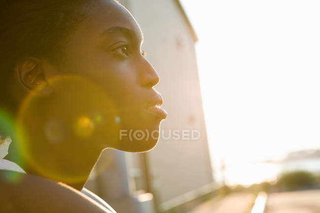 Profile of a young woman in sunlight — Stock Photo