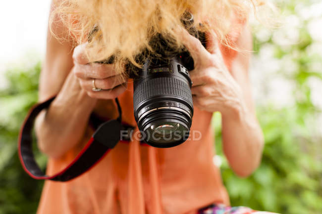 Cropped shot of woman with red hair photographing downward with digital SLR — Stock Photo
