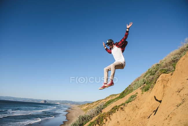 Junger Mann springt sandigen Hügel hinunter, in der Luft — Stockfoto