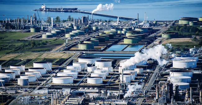 Réservoirs de stockage de pétrole dans une raffinerie côtière — Photo de stock