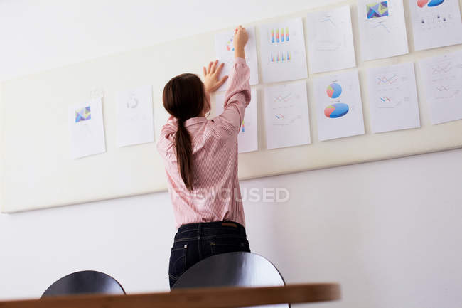 Businesswoman tacking up sign in office — Stock Photo
