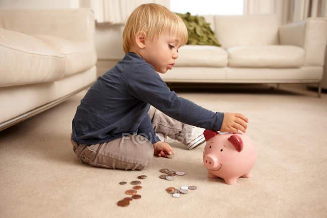 Chico poniendo monedas en hucha - foto de stock