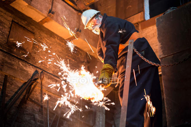Worker cleaning surface of molten metal in foundry — Stock Photo