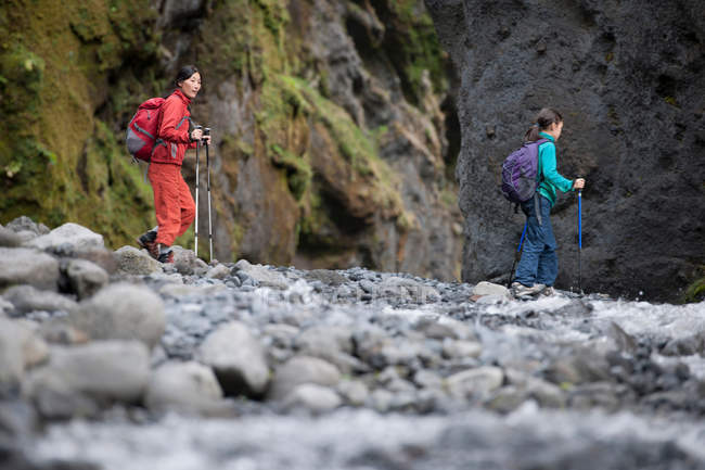 Mother and daughter hiking rocky river — Stock Photo