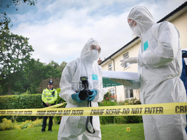 Forensic scientists in discussion at crime scene, one holding camera, policeman in background — Stock Photo
