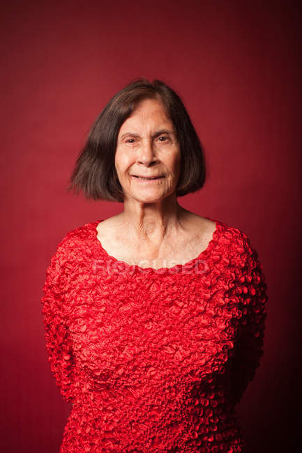 Portrait d'une femme senior sur fond rouge — Photo de stock
