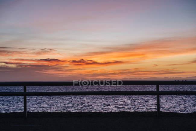 Clôture silhouettée et mer au crépuscule — Photo de stock