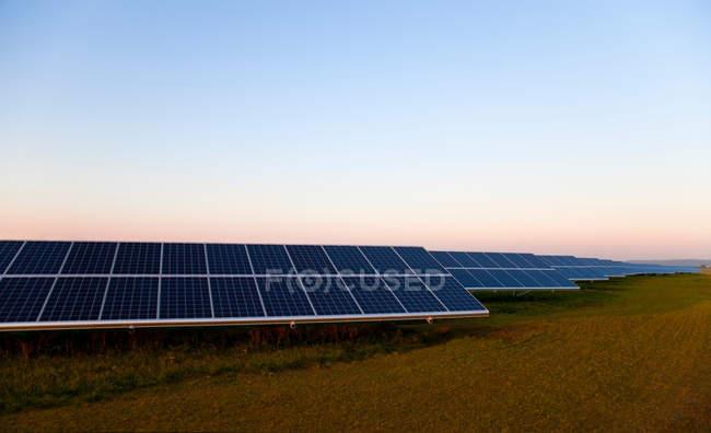 Solar panels on grass under sunset sky — Stock Photo