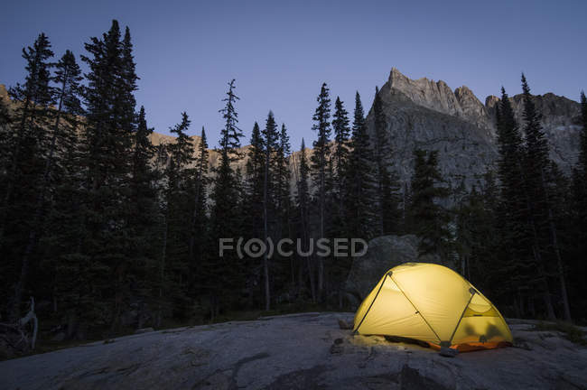 Glowing tent in mountainous landscape at evening — Stock Photo