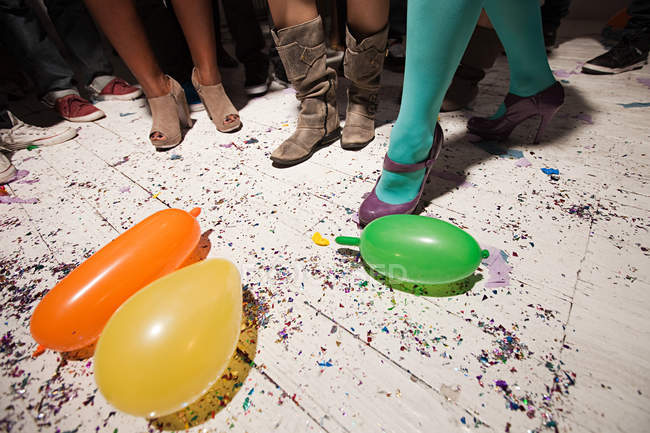 People dancing at party with balloons on floorboards — Stock Photo
