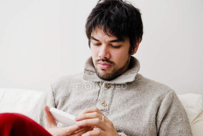Uomo che per mezzo del telefono cellulare sul sofà — Foto stock
