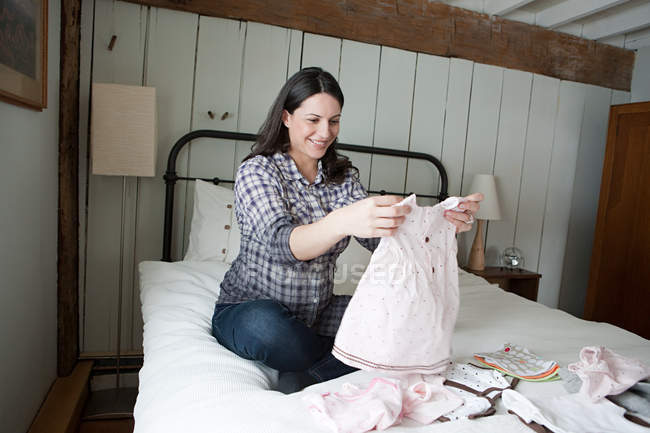 Expectant mother looking at baby clothes — Stock Photo