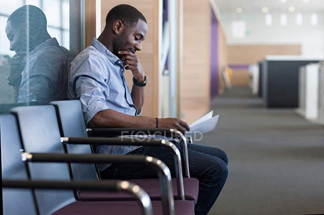 Человек, сидящий на стуле, чтение документа — стоковое фото