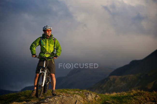 Горный байкер на травянистом склоне — стоковое фото