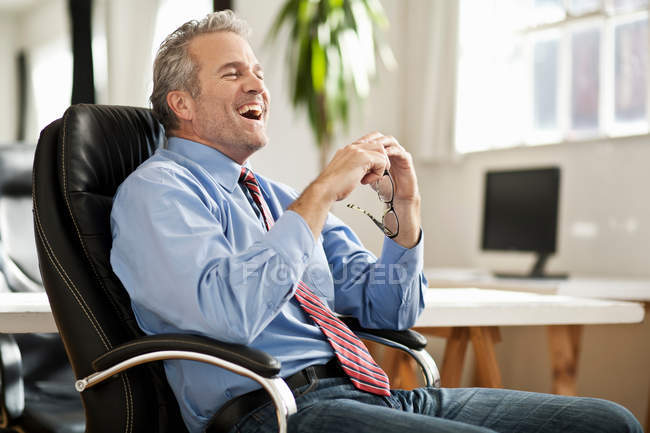 Businessman laughing at desk — Stock Photo