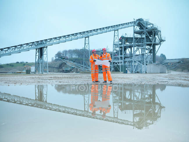 Quarryman and assistant looking at plans in front of quarry screening plant — Stock Photo