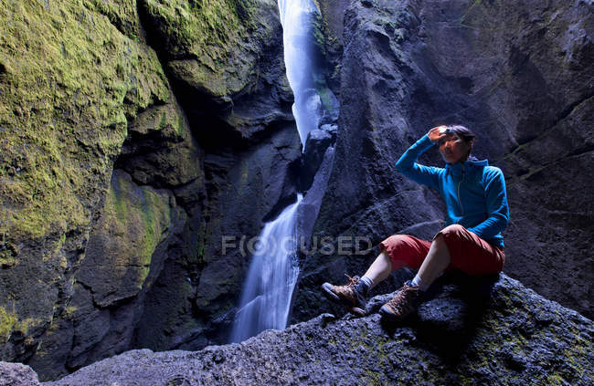Woman in rocky valley with waterfall — Stock Photo