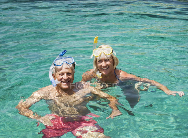 Mature couple swimming with snorkels — Stock Photo