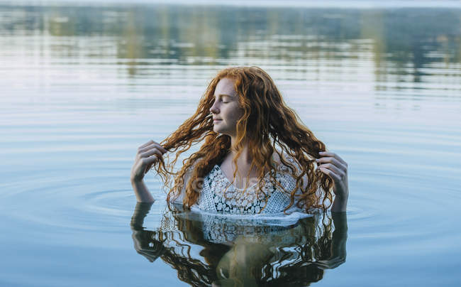 Head and shoulders of beautiful young woman with long red hair in lake — Stock Photo