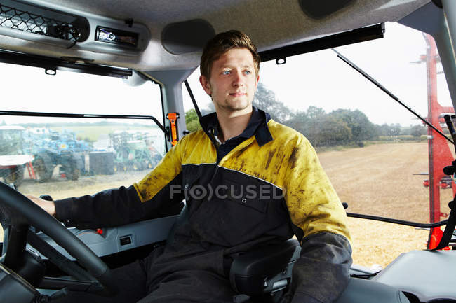 Farmer driving tractor in field — Stock Photo