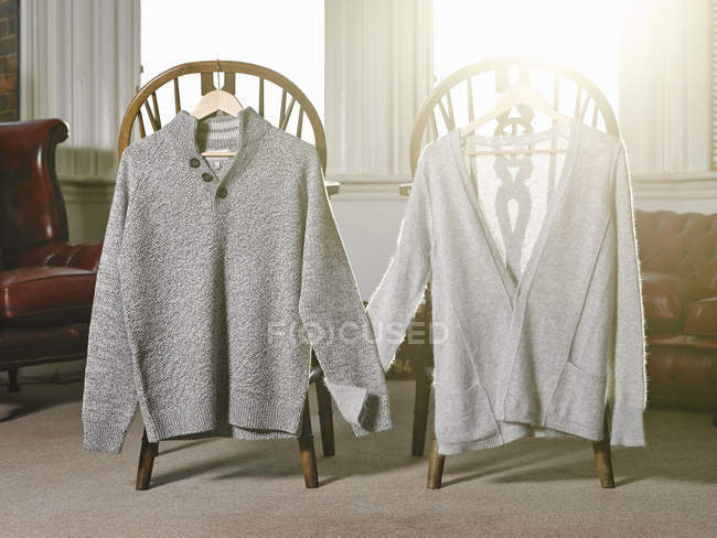 Sweaters on coat hangers — Stock Photo