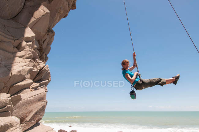 Rock climber abseiling jagged cliff — Stock Photo