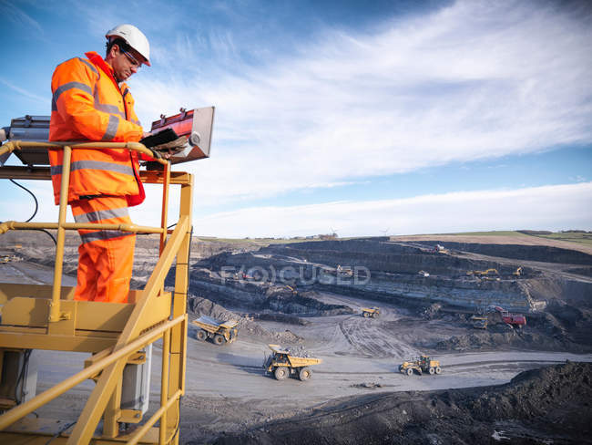 Ecologist using digital tablet surveying surface coal mine site from platform, elevated view — Stock Photo