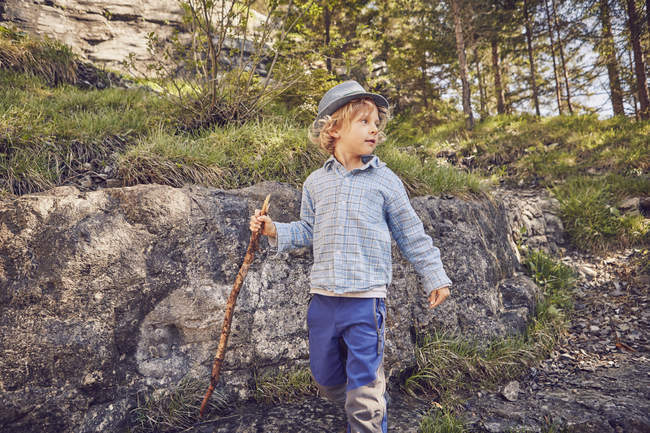 Un jeune garçon, tenant un bâton, explorant la forêt — Photo de stock