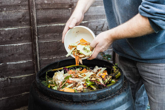 Man adding to compost bin outdoors — Stock Photo