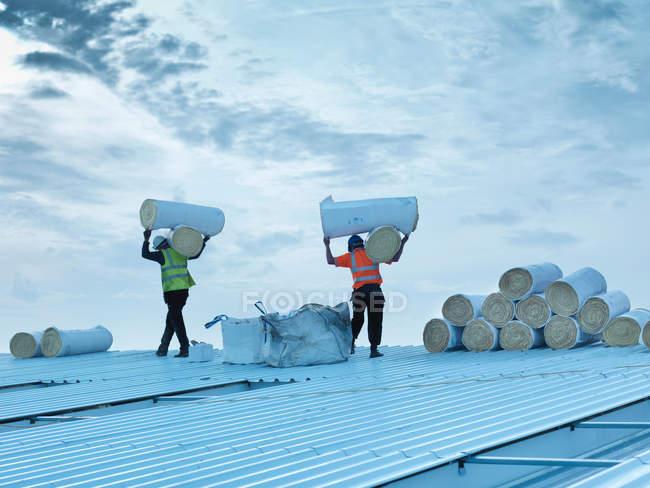 Trabalhadores que transportam rolos de isolamento para instalar no telhado da fábrica — Fotografia de Stock
