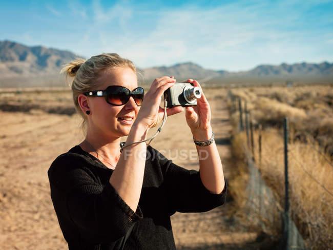 Donna che scatta foto in campo rurale — Foto stock