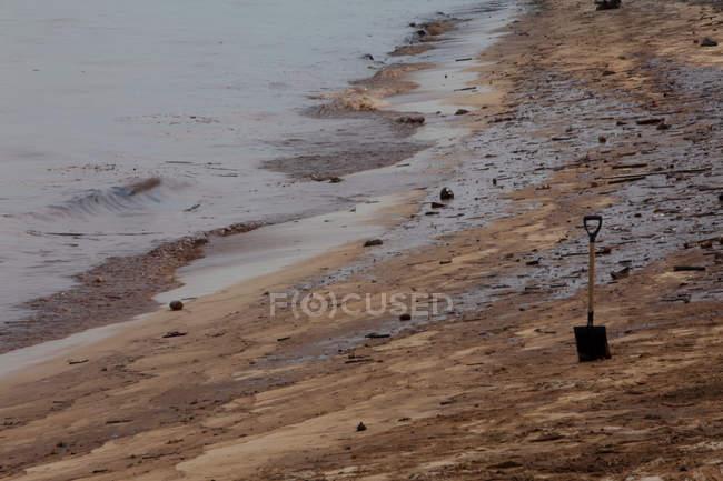 Pala en la arena en la playa aceitosa - foto de stock