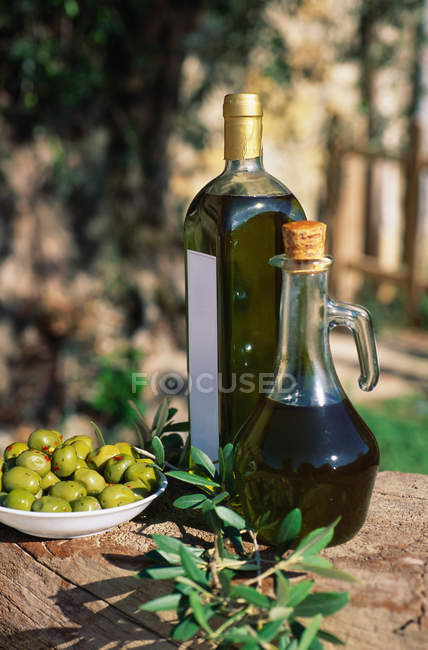 Fresh olives and oil bottles on table — Stock Photo