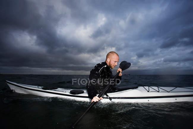 L'uomo in kayak contro il cielo drammatico — Foto stock