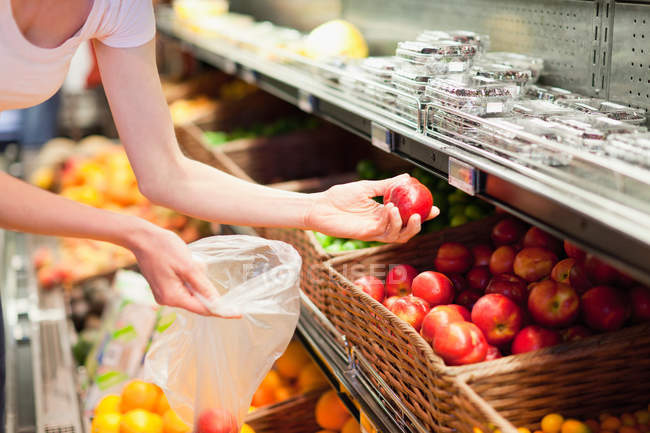 Woman selecting fruit at grocery store — Stock Photo