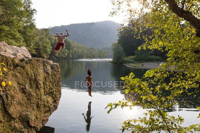 Junges paar springen vom Felsvorsprung, Hamburg, Pennsylvania, Usa — Stockfoto
