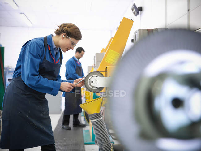 Male and female engineers using polishing tools in engineering factory — Stock Photo