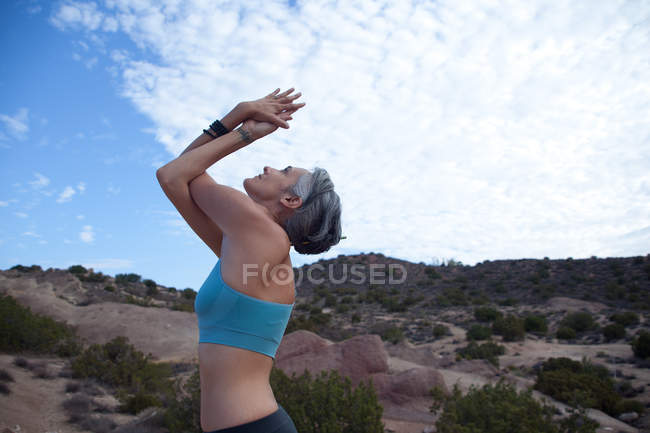 Side view of woman doing yoga at Vazquez Rocks, LA — Stock Photo