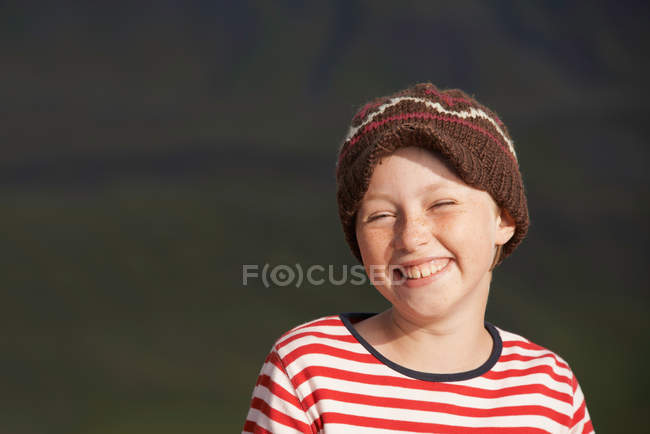 Chica sonriente con gorra de punto - foto de stock