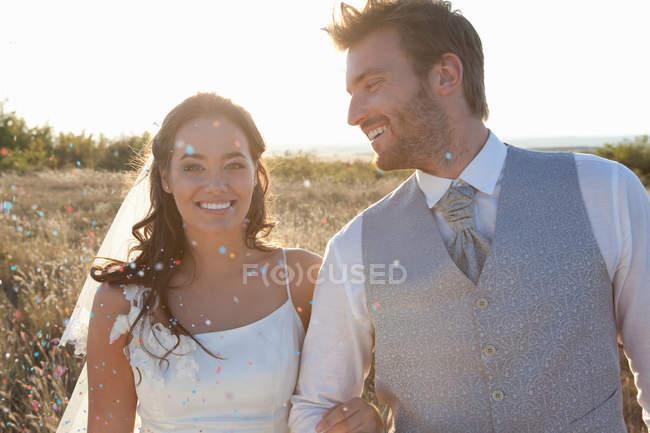 Couple nouvellement marié marchant dans les confettis — Photo de stock