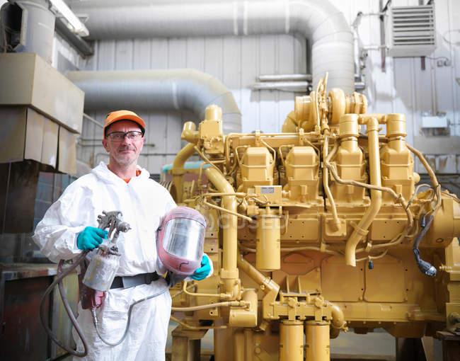 Рабочий в распылительной кабинке с двигателем — стоковое фото