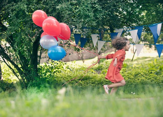 Девушка держит кучу воздушных шаров на улице — стоковое фото