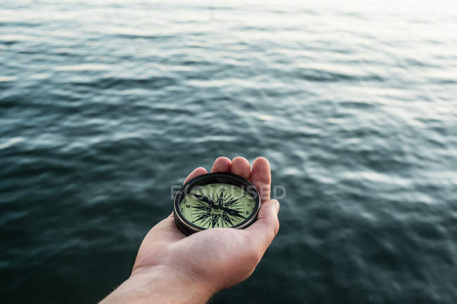 Close-up of hand holding compass — Stock Photo