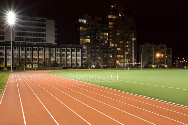 Беговая дорожка и футбольное поле освещены ночью — стоковое фото