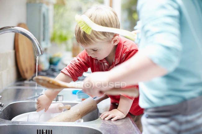 Children washing dishes together — Stock Photo