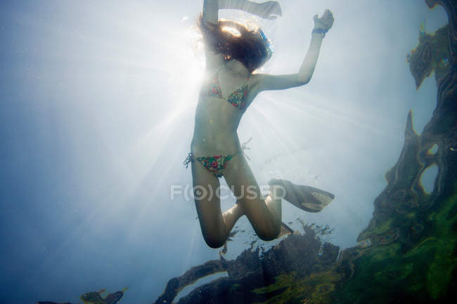 Low angle underwater view of girl snorkeling in tropical waters — Stock Photo