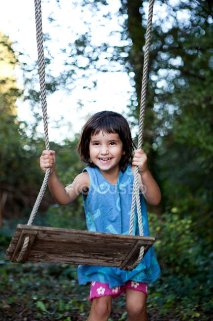 Little girl with swing, laughing — Stock Photo