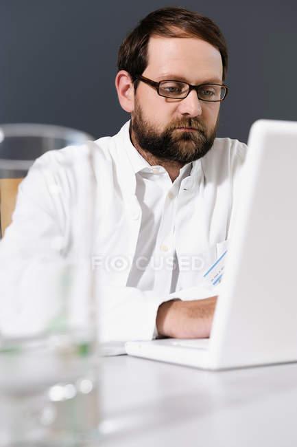 Doctor usando portátil en el escritorio - foto de stock